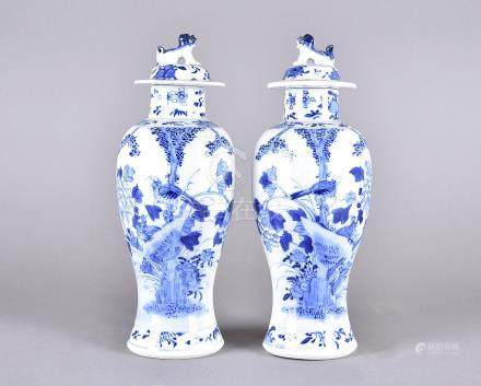 A pair of 19th century blue and white baluster porcelain vases and covers, decorated with exotic
