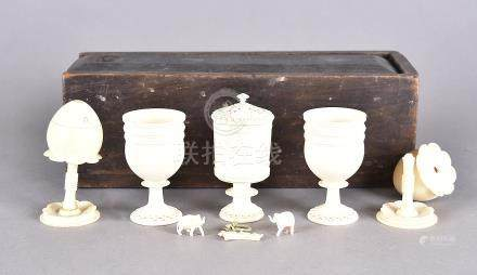A late 19th century Indian ivory cruet, egg cups in a wooden pencil box