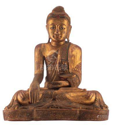 A Thai gilt lacquered wooden seated Buddha with glass inlay, H 66,5 - W 60 - D 34,5 cm