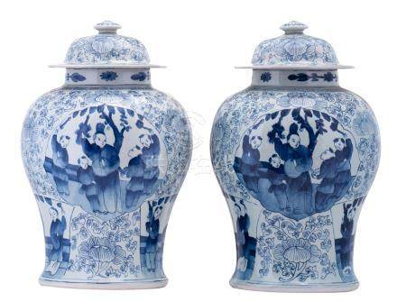 A pair of Chinese blue and white floral decorated vases and covers, the roundels with figures in a garden, H 42 cm