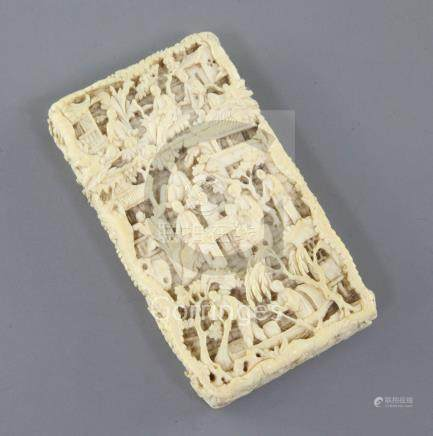 A Chinese export ivory card case, 19th century, carved in high relief with figures amid pavilions