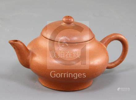 A small Chinese Yixing pottery teapot and cover, with ring shaped handle, impressed maker's mark