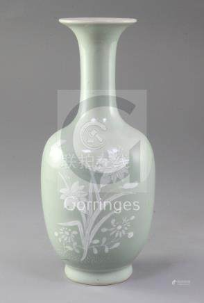 A Chinese celadon ground bottle vase, 19th century, decorated in white slip with flowers and foliage