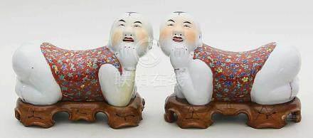 Paar figürliche Hochzeits-Kopfstützen.Porzellan. Je in Form eines liegenden Knaben, den Kopf mit