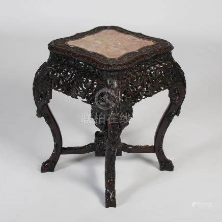 A rare Chinese dark wood urn stand, Qing Dynasty, the shaped square top with a mottled red and white