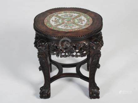 A Chinese dark wood jardiniere stand, Qing Dynasty, the shaped circular top centred with a famille