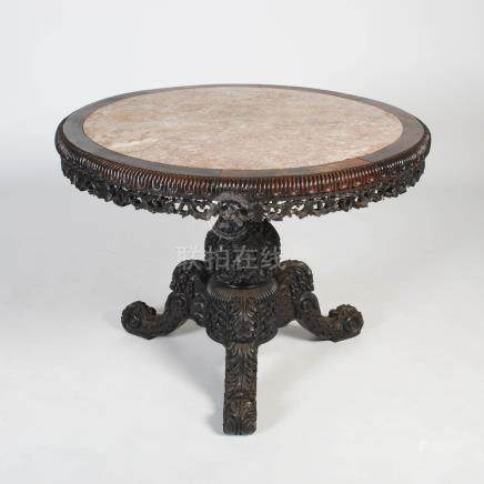 An impressive Chinese dark wood round table, Qing Dynasty, the circular top with a mottled red and