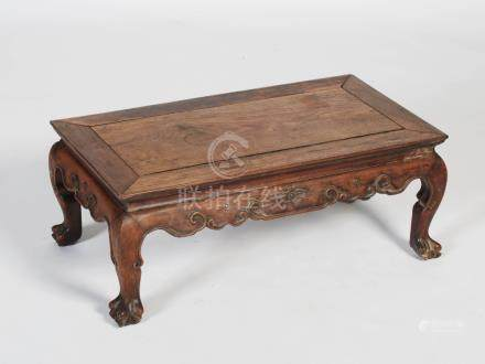 A Chinese dark wood Kang table, late Qing Dynasty, the rectangular panel top above a frieze carved