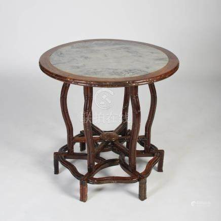 A Chinese dark wood round table, Qing Dynasty, the circular detachable top with a mottled white