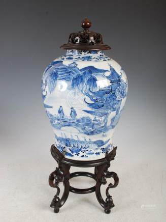 A Chinese porcelain blue and white jar, pierced wood cover and stand, Qing Dynasty, decorated with