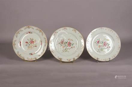 Assiette ronde en porcelaine blanche à décor polychrome de bouquet retenu par u