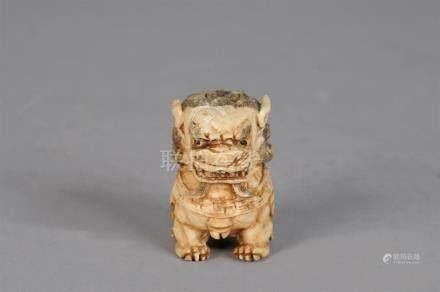 Petit sujet en ivoire sculpté patiné à rehauts bruns stlysié d'un Chien de Fo a