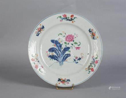 Assiette ronde en porcelaine à décor polychrome de fleurs et feuillages.Chine,