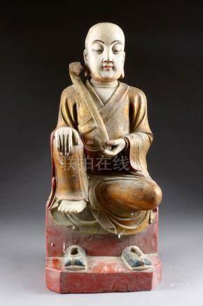 Moine assis. Vêtu de la robe monastique, un sceptre Ru-Yi dans la main gauche.
