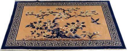 Carpette Chine. Elle présente un arbre fleuri animé par des oiseaux. Bordure gé