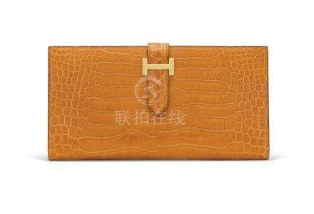 A SHINY SAFRAN POROSUS CROCODILE BÉARN WALLET WITH GOLD HARDWARE