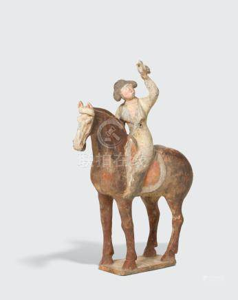 A PAINTED POTTERY FIGURE OF A YOUNG EQUSTRIENNE HOLDING A BIRD   Tang dynasty