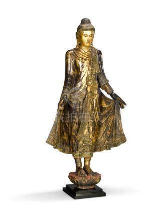 A polychrome and gilt lacquered wood figure of standing Buddha Burma, Mandalay style, 20th century
