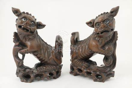 Pair of Oriental carved wooden figures of Buddhist lions, glass eyes,