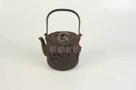 A Japanese iron kettle, 19th century, with a swing handle, the body decorated with crabs,