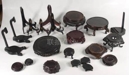 A quantity of Chinese wooden vase and plate stands.