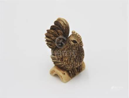 A bone netsuke carved as a hen, early 20th century, height 4.3cm, width 2.4cm.