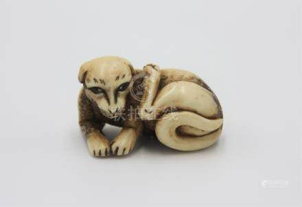 A bone netsuke carved as a dog, early 20th century, height 2cm, width 4.2cm.