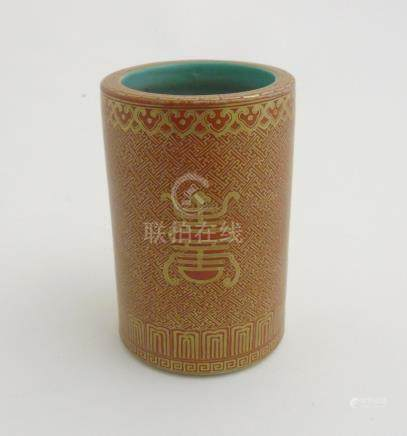 A Chinese brush pot of cylindrical form in burnt orange with gilt coloured highlights,