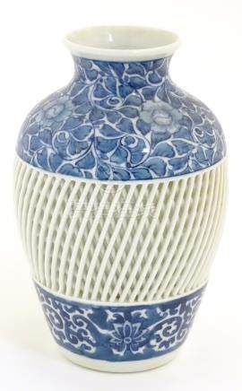 A blue and white Chinese baluster vase decorated with a floral pattern and a reticulated banded