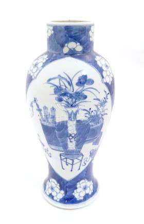 A Chinese, blue and white baluster vase decorated with prunus flowers,