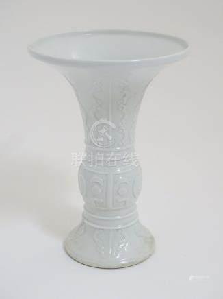 A Chinese white glazed Gu vase of archaic bronze design,