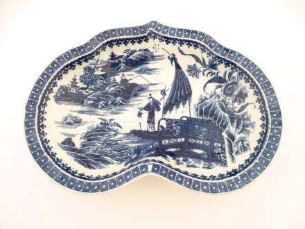 An oriental blue and white kidney shaped dish decorated with oriental scenes of fishing, pagodas,
