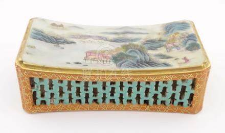 A Chinese famille rose headrest with a gently sloped surface decorated with a landscape,