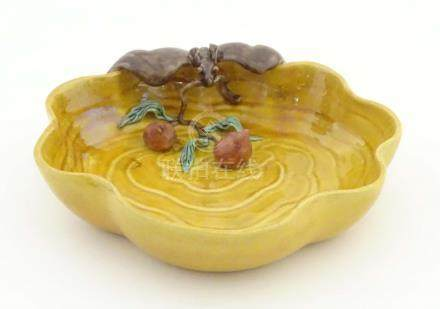 A Chinese wavy edged yellow brush wash dish with bat and fruit decoration,