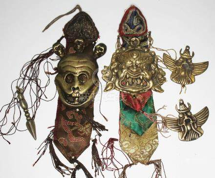 Five Tibetan/Nepalese items comprising two protector amulets, a miniature brass phurba, a Buddhist 4