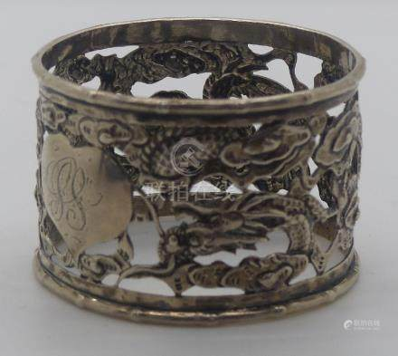 Chinese white metal embossed and pierced napkin ring with dragon decoration, with Chinese