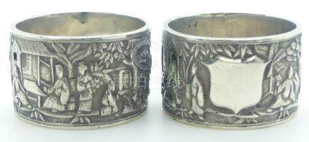 Pair of Chinese white metal napkin rings decorated with figures, buildings and trees, with Chinese