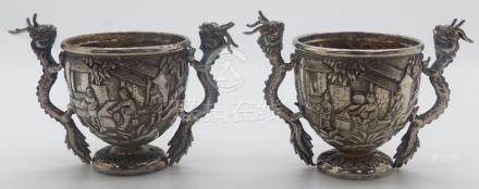 Pair of Chinese white metal open salts with embossed decoration of figures and buildings, the