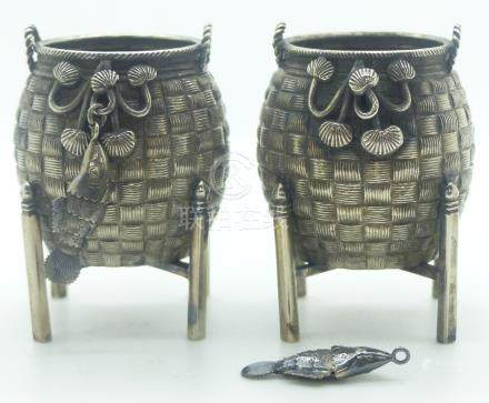 Pair of Chinese white metal salts formed as woven baskets on stands with articulated hanging fish,