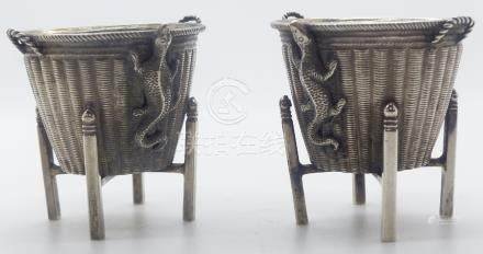 Pair of Chinese white metal salts formed as woven tapered baskets on stands with lizards to one