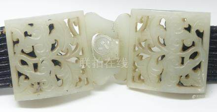 A 19th Century Chinese pierced and carved jade belt buckle in two parts, on later belt, 4.5 x 11 cm.