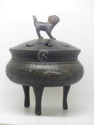 A bronze tripod censer / koro decorated with birds among bamboo friezes and with Dog of Fo finial,