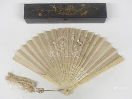 A 19th/20thC Chinese carved bone fan decorated with dragons, in lacquer box, length 22cm
