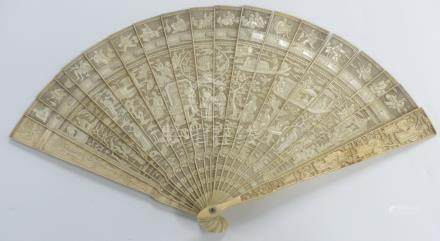A 19thC Chinese ivory fan of 21 sticks, each with carved decoration of figures, dragons, boats