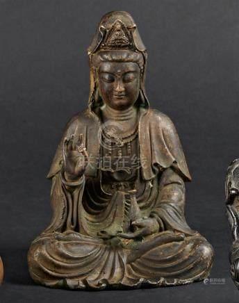 § CHINE - XIXe siècleGuanyin en bronze à patine brune assise, tenant dans sa ma