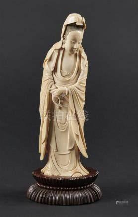 CHINE - Vers 1900Statuette de Guanyin debout en ivoire, les mains jointes devan