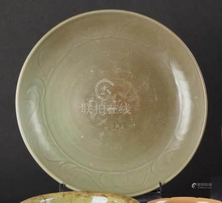 CHINE - XVe sièclePlat circulaire en grès émaillé céladon à décor incisé sous c