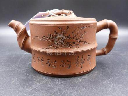 A YIXING TEAPOT WITH BAMBOO SPOUT AND HANDLES, THE TWO SECTION CYLINDRICAL BODY INSCRIBED ABOUT