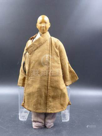 A CHINESE DOOR OF HOPE MISSION CARVED WOODEN DOLL CLOTHED IN A BROWN COAT OVER A BLUE SUIT.