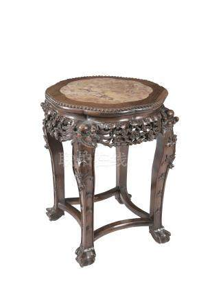 A CHINESE PADOUK JARDINIERE STAND, the shaped circular top with inset marble above a carved and